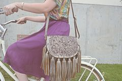 Woman sitting in a bicycle with violet skirt. A woman riding a bicycle. She is wearing a violet skirt and a multicolor shirt. she has a silver leather bag. Retro Royalty Free Stock Image