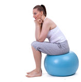 Woman sitting on the big blue ball Royalty Free Stock Photos