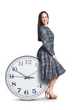 Woman sitting on big clock Stock Photography