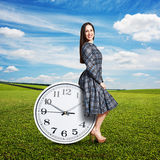 Woman sitting on the big clock Royalty Free Stock Photography