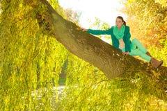 Woman sitting on big tree trunk Royalty Free Stock Image