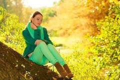 Woman sitting on big tree trunk Stock Images
