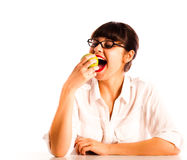 Woman sitting biting a green apple wearing glasses Royalty Free Stock Photography