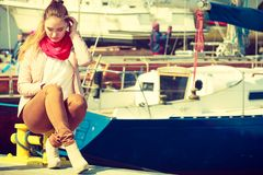Woman sitting on bitt in marina Royalty Free Stock Images