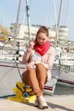 Woman sitting on bitt in marina Stock Images