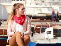 Woman sitting on bitt in marina Stock Photography