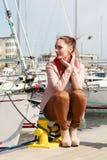 Woman sitting on bitt in marina Royalty Free Stock Photos