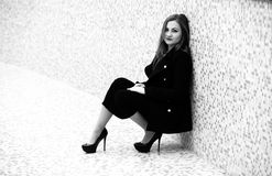 Woman sitting in black dress and leaning against tiled wall Royalty Free Stock Images