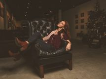 Woman Sitting on Black Leather Armchair Stock Image