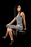 Woman sitting black white stripes dress Stock Images