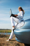 Woman sitting on the blue car with laptop Stock Image
