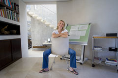 Woman sitting by blue prints on drafting board in home office, smiling portrait Stock Photo