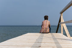Woman sitting on a boardwalk Stock Photography