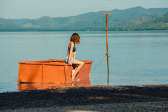 Woman sitting in boat on beach Stock Images