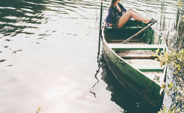 Woman sitting in boat and enjoy moments of relaxation. Woman sitting in an old boat near the shore and enjoy moments of relaxation at sunset Royalty Free Stock Images
