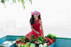 Woman sitting on a boat with vegetables Royalty Free Stock Photo