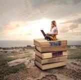Woman sitting on books Stock Photo