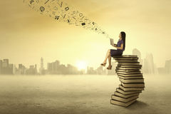 Woman sitting on books and send message Stock Images