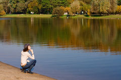 Woman sitting on the border of a river. Young pretty woman sitting on the border of a river Royalty Free Stock Image