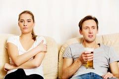 Woman sitting bored while man watching sports Stock Photo