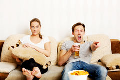 Woman sitting bored while man watching sports Stock Image