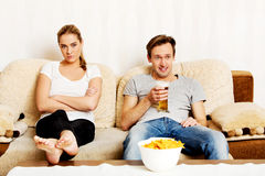 Woman sitting bored while man watching sports Stock Photography