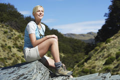 Woman Sitting On Boulder In Forest Stock Photo