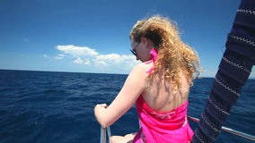 Woman sitting on bow of sailing boat enjoying view of sea stock footage