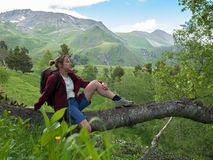 Woman sitting on the branch of the birch Stock Photo