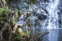 Woman sitting on the branches of a tree near the forest waterfall pond. Stock Images