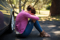 Woman sitting by breakdown car Royalty Free Stock Photography