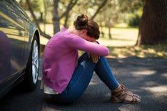 Woman sitting by breakdown car. Sad woman sitting by breakdown car Royalty Free Stock Photography