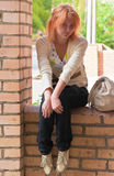 Woman sitting on brick wall Stock Photography