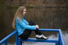 Woman sitting on the bridge Stock Photography