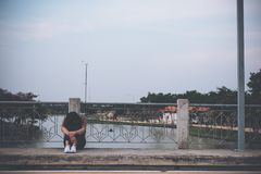 A woman sitting on the bridge with feeling sad stock photos