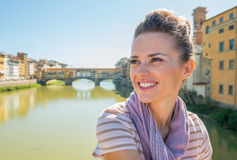 Woman sitting on bridge overlooking ponte vecchio Stock Images