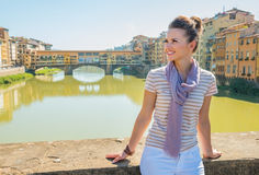 Woman sitting on bridge overlooking ponte vecchio Royalty Free Stock Image