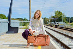 Woman sitting with brown bag and suitcase Stock Photography