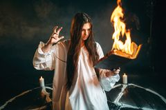 Woman sitting in burning pentagram circle, magic. Young woman in white shirt sitting in the center of burning pentagram circle and reads spellbook, gark magic Stock Images