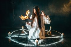 Woman sitting in burning pentagram circle, magic. Young woman in white shirt sitting in the center of burning pentagram circle and reads spellbook, gark magic stock photos