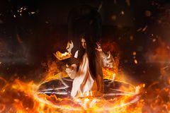 Woman sitting in burning pentagram circle, magic. Young woman in white shirt sitting in the center of burning pentagram circle and reads spellbook, gark magic royalty free stock image