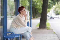 Woman sitting at bus stop and waiting Stock Photography