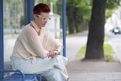 Woman sitting at bus stop and waiting Stock Photo