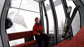 A woman sitting on a Cable car during a snow storm stock video