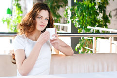 Woman sitting in a cafe with a coffe Royalty Free Stock Image