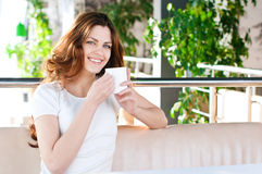 Woman sitting in a cafe with a coffe Stock Images