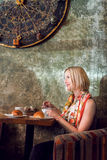 Woman sitting in a cafe and drink coffee. Royalty Free Stock Photo