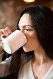 Woman sitting in a cafe drinking c Royalty Free Stock Images