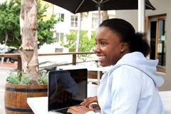 Woman sitting at cafe garden surfing internet Royalty Free Stock Photography