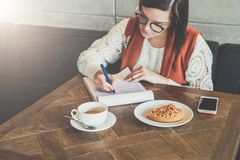 Woman is sitting in cafe at table, working. Girl fills out an application, signs documents, draws up resume. Royalty Free Stock Images